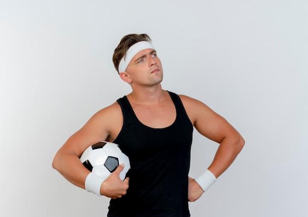 Nachdenklicher junger hübscher sportlicher mann, der stirnband und armbänder hält, die fußball halten und hand auf taille setzen, die seite lokalisiert auf weißer wand betrachtet