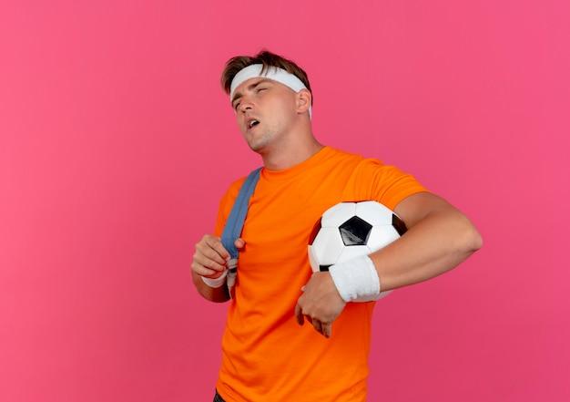 Nachdenklicher junger hübscher sportlicher mann, der stirnband und armbänder und rückentasche hält, die fußball und riemen der rückentasche hält, die gerade lokal auf rosa wand suchen