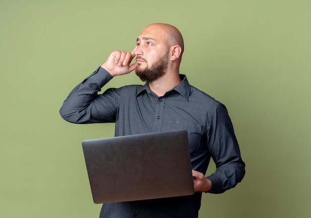 Nachdenklicher junger kahler callcenter-mann, der laptop hält, der seite mit finger auf tempel lokalisiert auf olivgrüner wand betrachtet