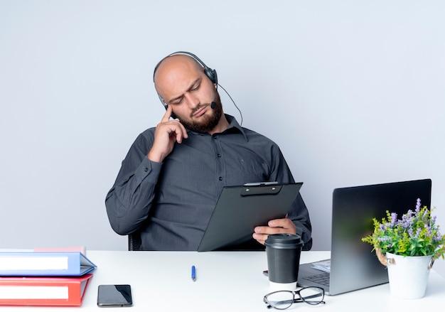 Nachdenklicher junger kahlköpfiger callcenter-mann, der headset trägt, das am schreibtisch mit arbeitswerkzeugen sitzt und die zwischenablage mit dem finger an der schläfe lokalisiert auf weißer wand hält