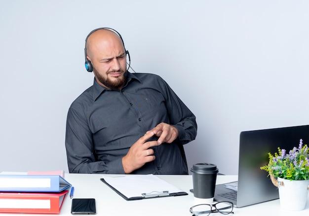 Nachdenklicher junger kahlköpfiger callcenter-mann, der headset trägt, sitzt am schreibtisch mit arbeitswerkzeugen, die finger zusammengehalten auf weißer wand halten