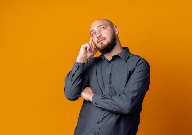 Nachdenklicher junger kahlköpfiger callcenter-mann, der mit geschlossener haltung steht und finger auf schläfe setzt, die lokal auf orange wand schaut