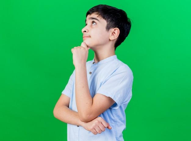Nachdenklicher junger kaukasischer junge, der in der profilansicht steht, das kinn berührt, das lokalisiert auf grüner wand mit kopienraum schaut