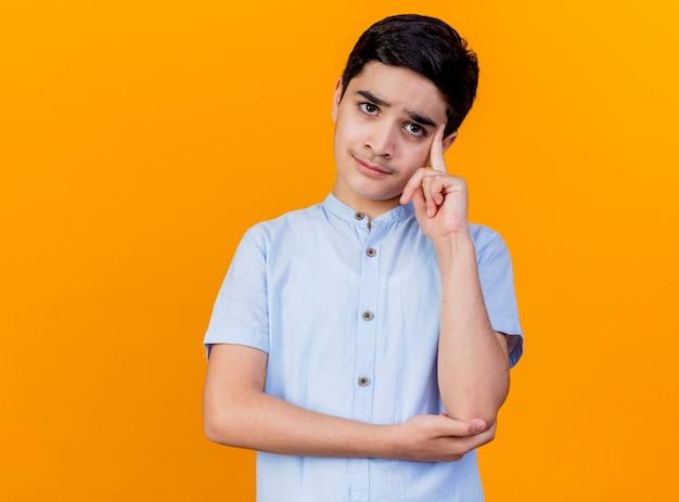 Nachdenklicher junger kaukasischer junge, der kamera betrachtet, denken denkgeste lokalisiert auf orange hintergrund mit kopienraum