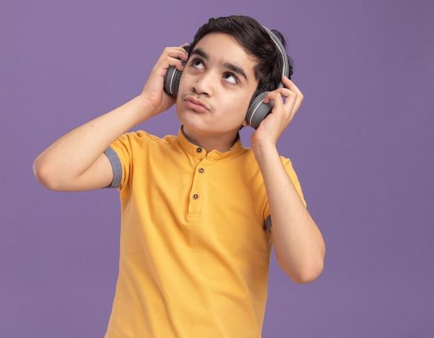 Nachdenklicher junger kaukasischer junge, der kopfhörer trägt und greift, die isoliert auf lila wand nachschlagen?