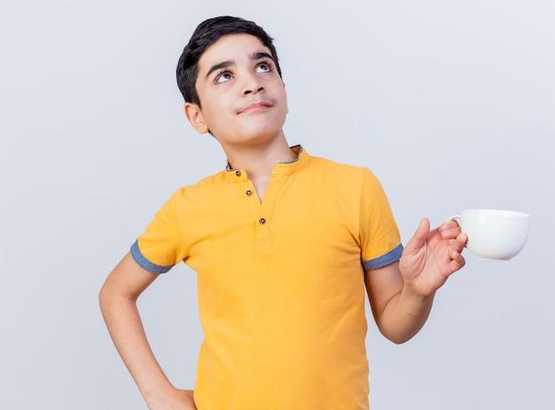 Nachdenklicher junger kaukasischer junge, der tasse hält hand auf taille hält und lokalisiert auf weißem hintergrund hält