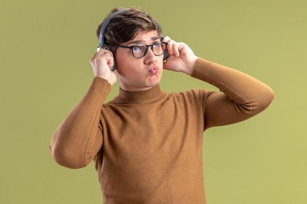 Nachdenklicher junger kaukasischer junge in optischer brille und auf kopfhörern, die nach oben schauen