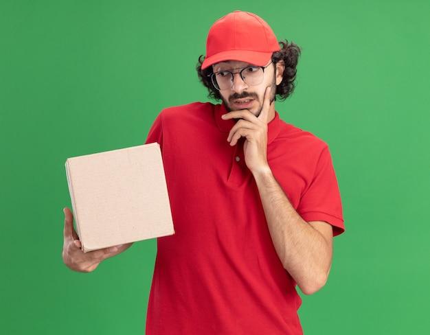 Nachdenklicher junger kaukasischer liefermann in roter uniform und mütze mit brille, die karton hält und betrachtet, der die hand am kinn hält, isoliert auf grüner wand