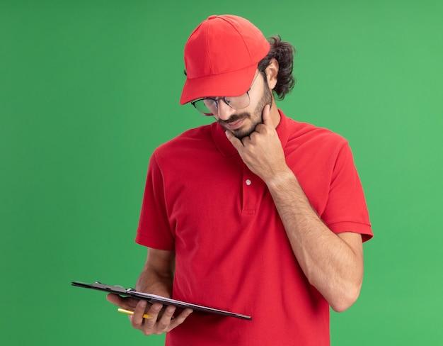 Nachdenklicher junger kaukasischer liefermann in roter uniform und mütze mit brille, die zwischenablage und bleistift hält, die hand am kinn hält und auf die zwischenablage schaut