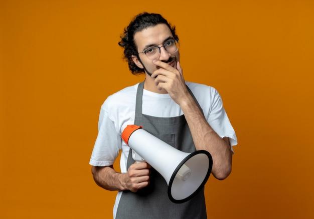 Nachdenklicher junger kaukasischer männlicher friseur, der uniform und brille trägt, lautsprecher hält und hand auf das kinn legt