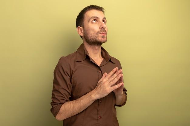Nachdenklicher junger kaukasischer mann, der hände zusammenhält, die lokal auf olivgrünem hintergrund mit kopienraum suchen