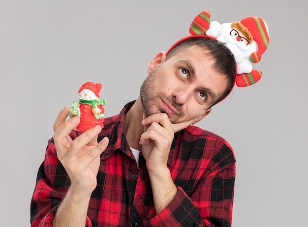 Nachdenklicher junger kaukasischer mann, der weihnachtsmann-stirnband hält, der schneemann-weihnachtsverzierung hält, die oben hält hand auf kinn lokalisiert auf weißem hintergrund hält