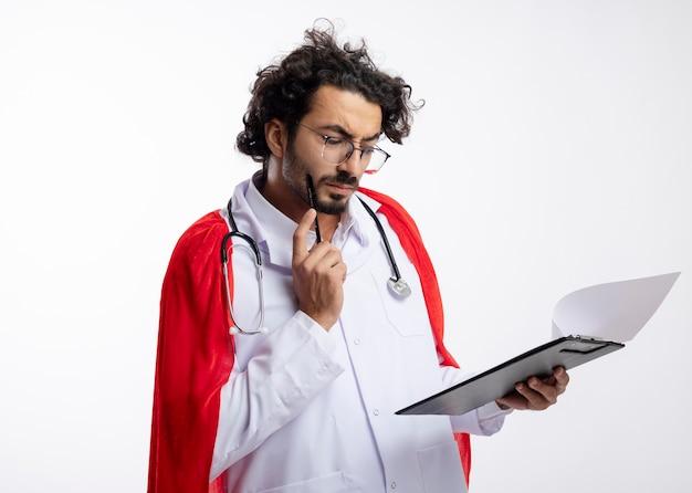 Nachdenklicher junger kaukasischer mann in der optischen brille, die arztuniform mit rotem umhang und mit stethoskop um hals trägt, setzt bleistift auf gesicht und schaut auf zwischenablage mit kopierraum