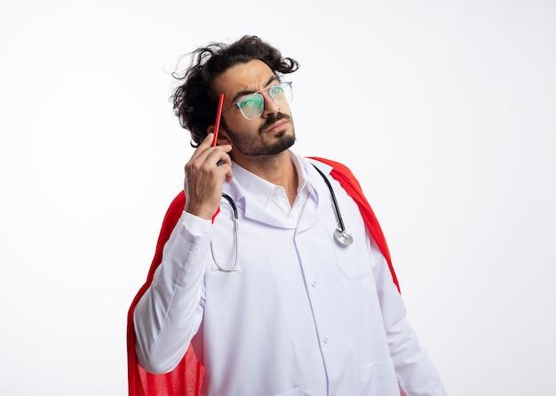 Nachdenklicher junger kaukasischer superheldenmann in optischer brille, der eine arztuniform mit rotem mantel trägt und mit stethoskop um den hals einen bleistift auf den tempel legt
