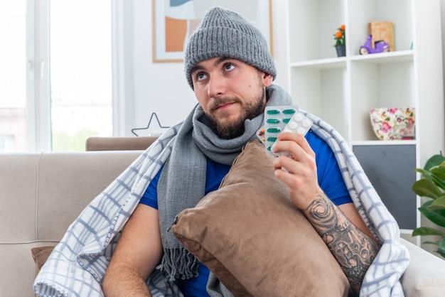 Nachdenklicher junger kranker mann mit schal und wintermütze, der in decke gehüllt auf dem sofa im wohnzimmer sitzt und kissen und pillen nach oben hält