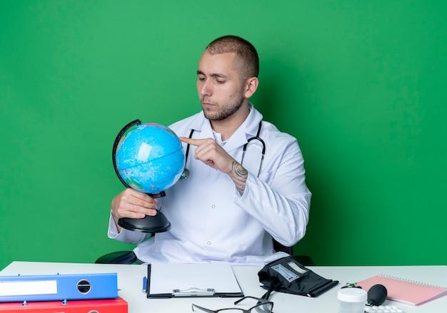 Nachdenklicher junger männlicher arzt, der medizinische robe und stethoskop trägt, sitzt am schreibtisch mit arbeitswerkzeugen, die globus halten und betrachten und finger auf ihn lokalisiert auf grüner wand setzen