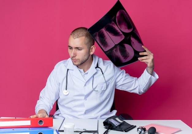 Nachdenklicher junger männlicher arzt, der medizinische robe und stethoskop trägt, sitzt am schreibtisch mit arbeitswerkzeugen, die röntgenaufnahme halten und schreibtisch lokalisiert auf rosa wand betrachten