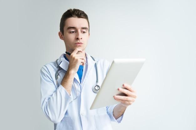 Nachdenklicher junger männlicher doktor, der tablet-computer verwendet