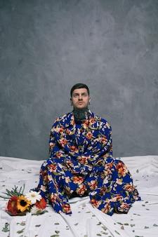 Nachdenklicher junger mann, der auf boden mit den gekreuzten beinen nahe den gerberablumen sitzt