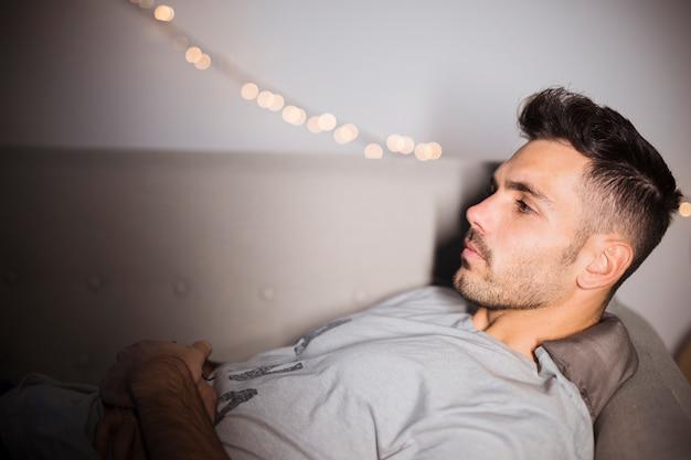 Nachdenklicher junger mann, der auf sofa liegt