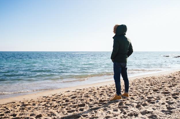 Nachdenklicher junger mann, der das meer, stehend auf dem sand betrachtet. rückansicht.