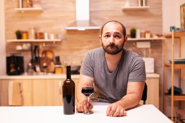 Nachdenklicher junger mann, der ein glas rotwein hält und über lebensprobleme nachdenkt