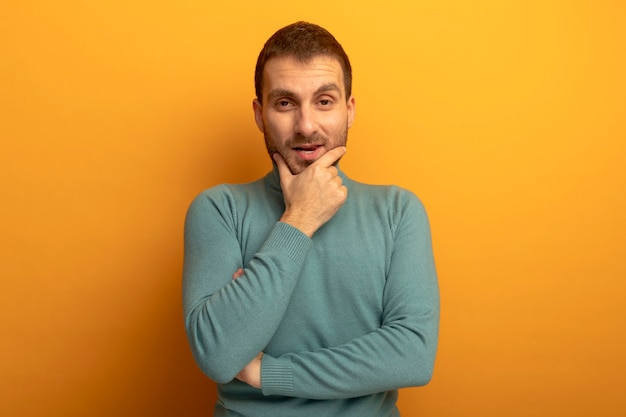 Nachdenklicher junger mann, der front betrachtet, die hand auf kinn lokalisiert auf orange wand setzt