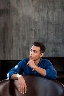 Nachdenklicher junger mann, der hinter dem stuhl gegen graue wand sitzt