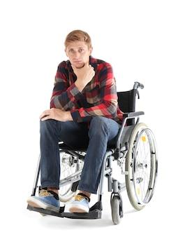 Nachdenklicher junger mann, der im rollstuhl auf weißem hintergrund sitzt