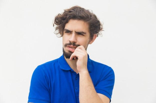 Nachdenklicher junger mann, der lippe reibt