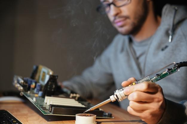 Nachdenklicher junger mann in hoodie und brille mit lötkolben zum reparieren des motherboards
