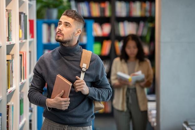Nachdenklicher junger mann mit buch und rucksack, der bücherregal betrachtet