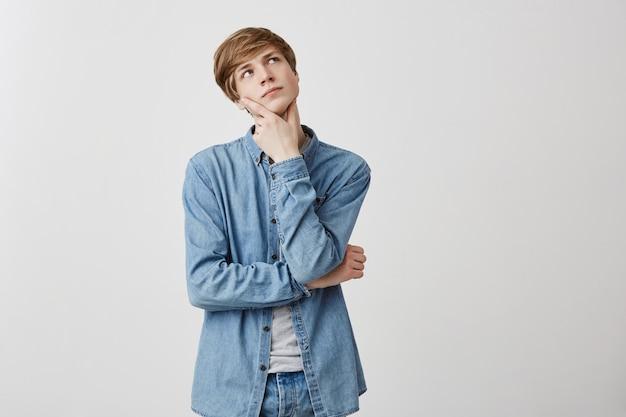Nachdenklicher junger mann mit hellem haar und blauen augen, ernstem gesichtsausdruck, schaut auf, hält die finger unter dem kinn, ist tief in gedanken versunken und denkt über zukünftige pläne nach. nachdenklicher kerl im jeanshemd