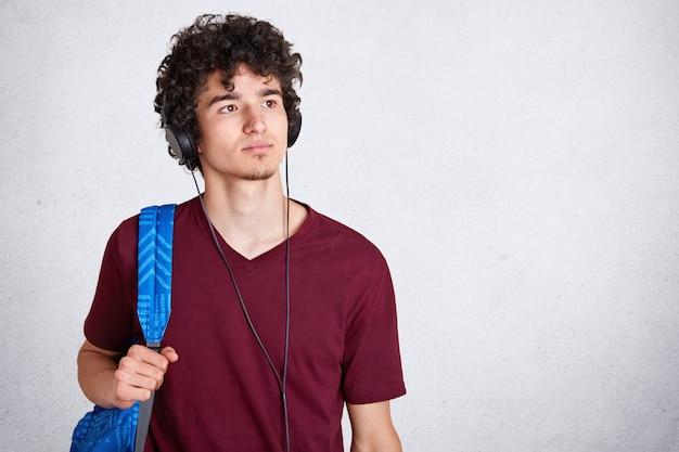 Nachdenklicher junger mann mit kopfhörern auf kopf und blauem rucksack