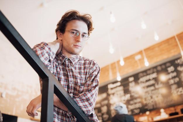 Nachdenklicher junger mann sitzt in der konditorei. sie trinkt kaffee, während sie auf jemanden wartet