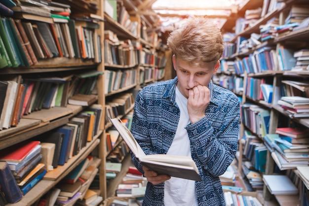 Nachdenklicher junger mann steht in einer gemütlichen bibliothek, liest ein buch und beißt sich auf die nägel.