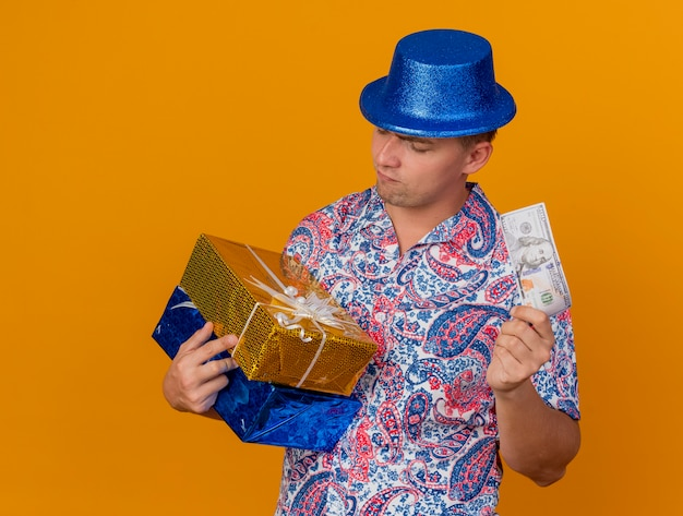 Nachdenklicher junger party-typ, der blauen hut hält und geschenkboxen mit bargeld auf orange isoliert betrachtet