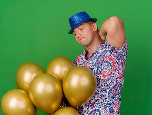 Nachdenklicher junger party-typ, der blauen hut trägt, der ballons hält und betrachtet und hand hinter kopf lokalisiert auf grün setzt