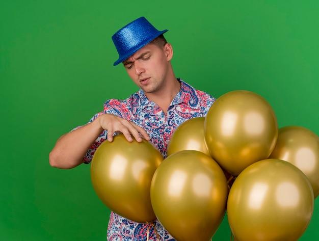 Nachdenklicher junger party-typ, der blauen hut trägt, der hinter luftballons steht und ballon isoliert auf grün packt