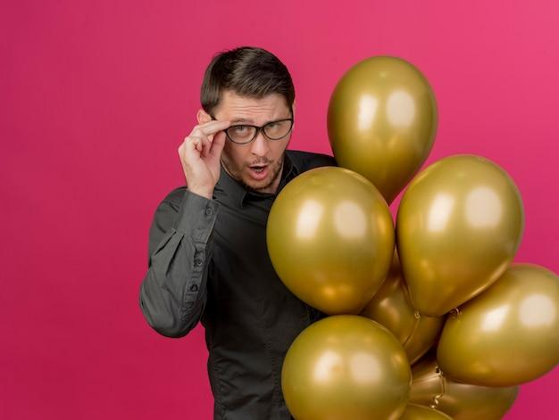 Nachdenklicher junger party-typ, der ein schwarzes hemd trägt, das luftballons hält und die auf rosa isolierte brille packt