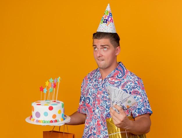 Nachdenklicher junger party-typ, der geburtstagskappe hält, die geschenke mit kuchen und bargeld lokalisiert auf orange hält