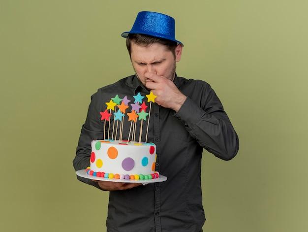 Nachdenklicher junger party-typ, der schwarzes hemd und blauen hut trägt, der kuchen hält und betrachtet, packte nase lokalisiert auf olivgrün
