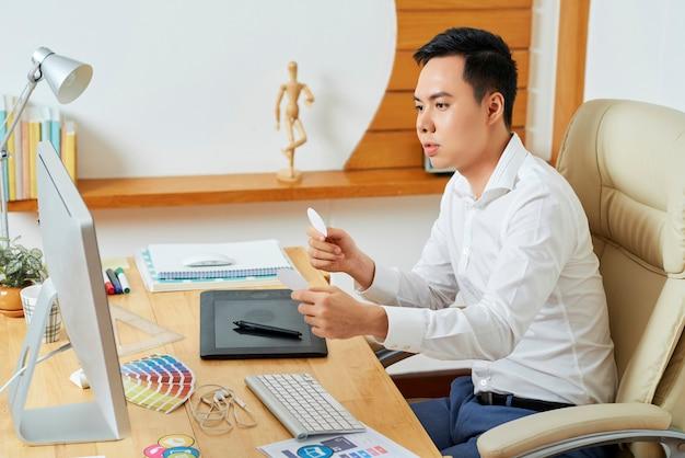 Nachdenklicher junger ui-designer, der perfekte symbole für neue anwendungen oder websites auswählt, an denen er arbeitet