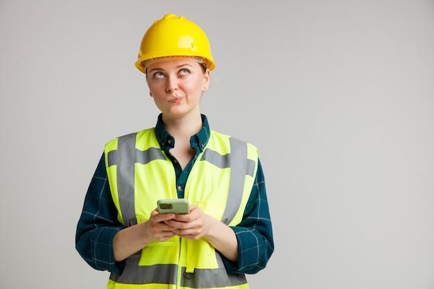 Nachdenklicher junger weiblicher bauarbeiter, der sicherheitshelm und sicherheitsweste hält, die mobiltelefon spitzend lippen nach oben schaut