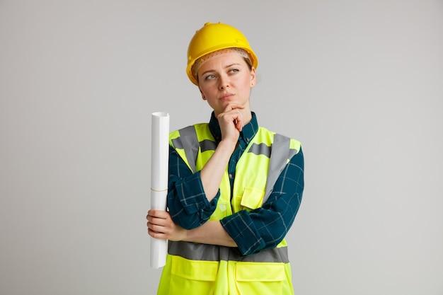 Nachdenklicher junger weiblicher bauarbeiter, der sicherheitshelm und sicherheitsweste hält, die papier hält hand auf kinn hält seite