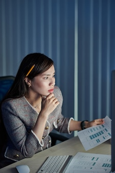 Nachdenklicher junger weiblicher projektmanager mit bleistift hinter ihrem ohr, der moblie anwendungsschnittstellenlayout mit endgültiger version auf computerbildschirm vergleicht