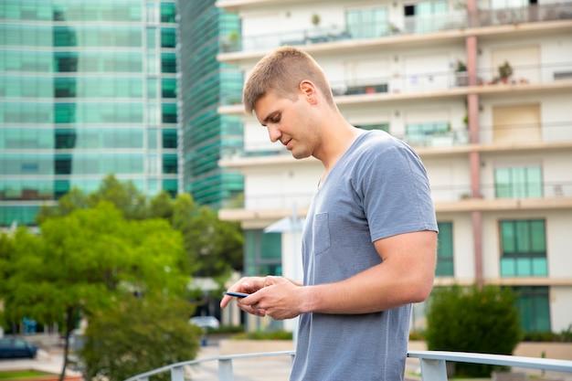 Nachdenklicher kaukasischer kerl, der smartphone in den städtischen einstellungen verwendet