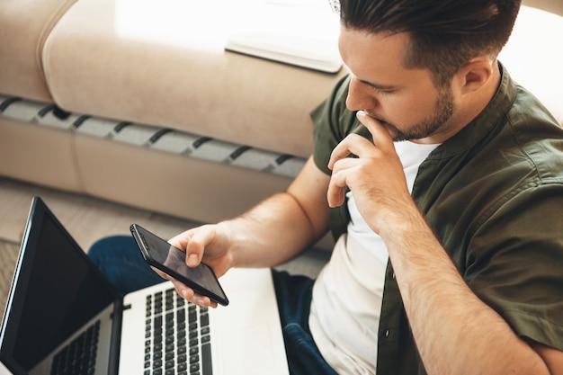 Nachdenklicher kaukasischer mann mit bart arbeitet von zu hause aus am computer, während er auf dem handy chattet