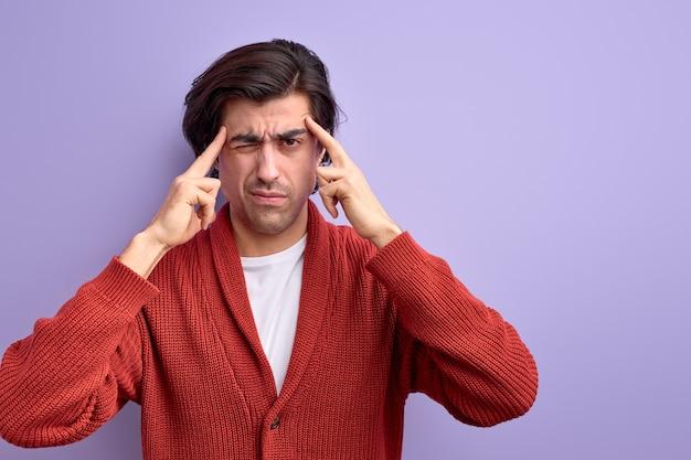 Nachdenklicher kaukasischer typ versucht sich an etwas zu erinnern, das finger an der schläfe hält