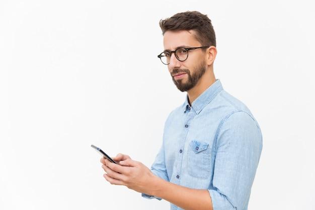 Nachdenklicher kerl, der den smartphone, textnachricht verwendet